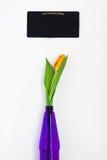 Eine gelbe Tulpe in einem Vase und violetten purpurroten in einem Kreidebrett für nicht Lizenzfreie Stockbilder