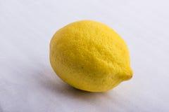 Eine gelbe Zitrone auf einer weißen Oberfläche Stockfotografie