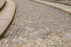 Eine gepflasterte Straße mit einer Beschränkung und einem intensiven ansteigenden Stockfoto
