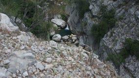 Eine Gesamtlänge eines Wasserfalls und des Gebirgssees stock footage