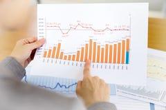 Eine Geschäftsfrau überreicht Papier- und Finanzdiagramm Stockfotografie