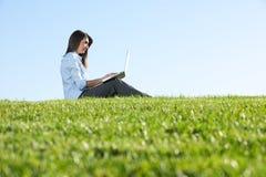 Eine Geschäftsfrau auf einem Laptop auf einem Gebiet stockfotos