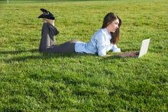 Eine Geschäftsfrau auf einem Laptop auf einem Gebiet lizenzfreie stockfotografie