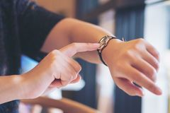 Eine Geschäftsfrau, die auf eine schwarze Armbanduhr auf ihrer Arbeitszeit zeigt Lizenzfreie Stockfotografie