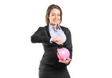 Eine Geschäftsfrau, die eine Münze in eine piggy Querneigung setzt Lizenzfreies Stockbild