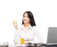 Eine Geschäftsfrau, die in einem Büro zu Mittag isst Lizenzfreie Stockfotografie