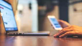 Eine Geschäftsfrau, die Handy bei der Anwendung des Laptops hält Lizenzfreie Stockfotos