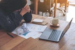 Eine Geschäftsfrau, die mit dem Gefühl frustriert und mit geschraubten hohen Papieren betont arbeitet stockfoto