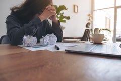Eine Geschäftsfrau, die mit dem Gefühl frustriert und mit geschraubten hohen Papieren betont arbeitet stockbilder