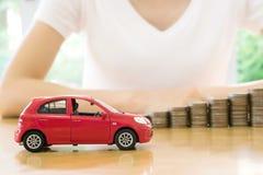 Eine Geschäftsfrau ein Spielzeugauto und ein Stapel Münzen Lizenzfreie Stockfotos