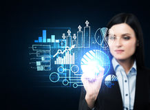Eine Geschäftsfrau im Gesellschaftsanzug schiebt das Element auf dem Hologramm mit Geschäftsikonen hinaus Lizenzfreie Stockfotos