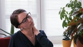 Eine Geschäftsfrau ist müde und hat Kopfschmerzen und Rückenschmerzen stock video