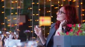 Eine Geschäftsfrau mit dem roten Haar, das durch Tabelle im Restaurant sitzt und ein Glas Champagner hält stock video