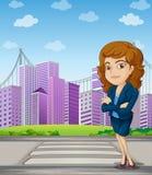Eine Geschäftsfrau mit einer Gesellschaftskleidung, die am Fußgänger steht Lizenzfreie Stockfotografie