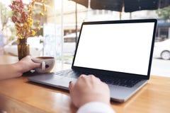 Eine Geschäftsfrau ` s Hand unter Verwendung des Laptops mit leerem weißem Tischplattenschirm beim Trinken des heißen Kaffees auf Lizenzfreies Stockbild