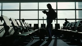 Eine Geschäftsfrau steht im Flughafenabfertigungsgebäude Benutzt eine Tablette, zusammen mit ihrer Reisetasche stock video footage