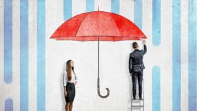 Eine Geschäftsfrau steht nahe einer Wand, in der ein Geschäftsmann einen riesigen roten Regenschirm zeichnet, der sie vom Regen b Stockfoto