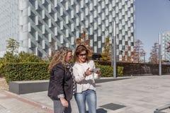 Eine Geschäftsfrau zeigt ein anderes etwas, das auf einer Tablette, vor einem Bürogebäude wichtig ist lizenzfreie stockfotos