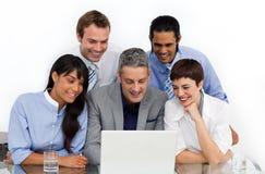Eine Geschäftsgruppe, die Verschiedenartigkeit unter Verwendung eines Laptops zeigt lizenzfreies stockfoto
