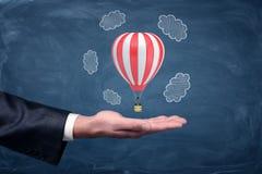 Eine Geschäftsmann ` s Hand oben gedreht und ein kleiner Luftballon, der über ihm auf Tafelhintergrund schwebt Lizenzfreie Stockfotografie