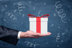 Eine Geschäftsmann ` s Hand oben gedreht und eine kleine Geschenkbox mit einem roten Bogen, der auf Tafelhintergrund steht Stockfotografie
