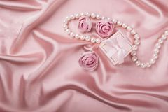 Eine Geschenkbox auf einem Satinhintergrund wird mit Blumen und Perlen verziert Flacher Plan stockbilder