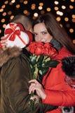 Eine Geschenkbox und Rosen haltene und beim Umarmen des Mannes lächelnde Frau lizenzfreies stockbild