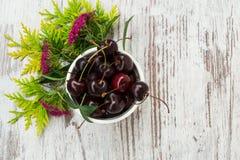 Eine geschmackvolle Kirsche in einer kleinen Schüssel mit Blumen Lizenzfreie Stockfotografie