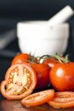 Eine geschnittenen und vier vollständigen Tomaten Lizenzfreies Stockbild