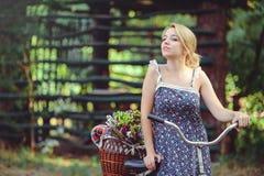 Eine gesunde Frau Schönheits-Sommermodellmädchen mit hellen Farben fahren Wald und Korb rad Artfreizeit Eine schöne Dame mit blon Stockfoto