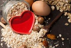 Eine gesunde trockene Hafermahlzeit mit Nuss und rotes Herz in einem hölzernen Löffel Stockbilder