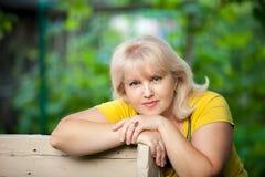 Eine gewachsene Frau auf einem grünen Hintergrund stockfoto