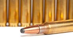Eine Gewehrkugel, die vor einer Reihe der Gewehrkugeln liegt stockbilder