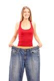 Eine Gewichtsverlustfrau, die ihr alte Jeans zeigt Stockfoto