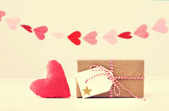 Eine Girlande von Herzen über einem kleinen als Geschenk eingepackten Kasten- und Textilherzen auf einem weg weißen Hintergrund Lizenzfreie Stockfotos