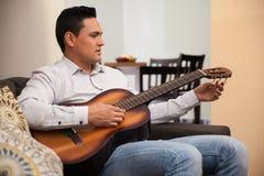 Eine Gitarre zu Hause abstimmen Stockfotografie