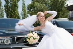 Eine glückliche Braut durch ein Auto Stockfotos