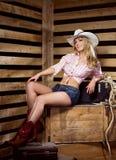 Eine glückliche Cowgirlfrau, die in einer Scheune aufwirft Stockfotografie