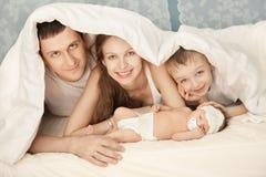 Eine glückliche Familie auf weißem Bett im Schlafzimmer Lizenzfreie Stockfotos
