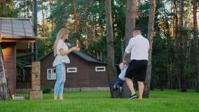 Eine glückliche Familie im Yard Ihres Hauses Der Vati dreht den Junge ` s Jungen herum, meine Mutter bereitsteht stock footage