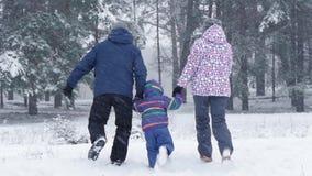 Eine glückliche Familie lässt Händchenhalten in Richtung zum Wald während Schneefälle im Winter laufen Freizeit, Tourismus und Sp stock video footage