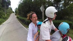 Eine glückliche Familie reitet ein Motorrad in den Tropen stock footage