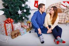 Eine glückliche Familie am Weihnachten im Haus auf dem Bodenblick auf einander Lizenzfreie Stockfotografie