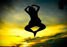 Eine glückliche Frau, die am Sonnenuntergang springt Stockfotografie