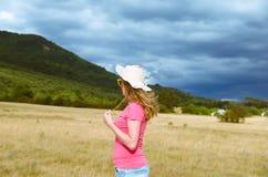 Eine glückliche Frau mit einem Hut schaut im Abstand, in der Natur Stockfotos