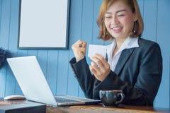 Eine glückliche Geschäftsfrau, die Arbeitsziele und in ihren Händen erzielt lizenzfreie stockfotografie