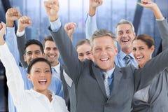 Eine glückliche Geschäftsgruppe, die Hände auf dem Boden gegen Gebäudefensterhintergrund anhebt Stockfotos