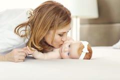 Eine glückliche Großmutter, die Babyenkel auf dem Bett küsst lizenzfreie stockfotografie