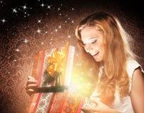 Eine glückliche Jugendliche, die ein Weihnachtsgeschenk öffnet lizenzfreies stockbild