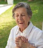 Eine glückliche lächelnde alte Frau mit geschlossenen Augen Stockfotos